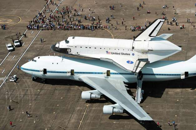 A crowd gathers around the space shuttle Endeavour, carried atop NASA's 747 Shuttle Carrier Aircraft, after landing at Ellington Field on Wednesday, Sept. 19, 2012, in Houston. Endeavour stopped in Houston on its way from the Kennedy Space Center to the California Science Center in Los Angeles, where it will be placed on permanent display. Photo: Smiley N. Pool, AP / Pool Houston Chronicle