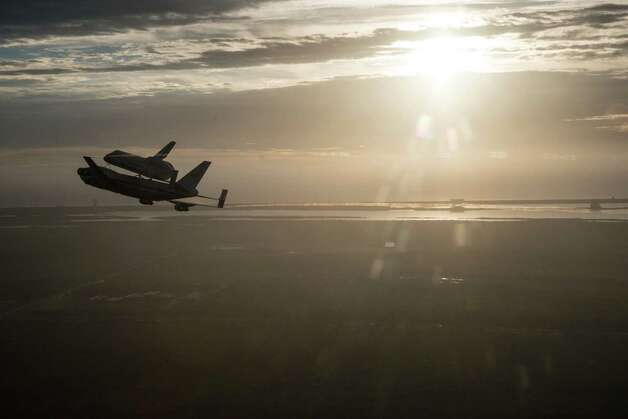 In this image provided by NASA the Space Shuttle Endeavour is ferried by NASA's Shuttle Carrier Aircraft (SCA) over the Kennedy Space Center in the early morning hours of Sept. 19, 2012 as it departs for California. Endeavour and the Shuttle Carrier Aircraft are in Houston after leaving Kennedy Space Center Wednesday. The ferry flight continues at dawn Thursday, heading to NASA Dryden, then on to Los Angeles Friday. This is the last flight for a space shuttle. Photo: ROBERT MARKOWITZ Robert Markowitz - NASA - JSC, AP / NASA