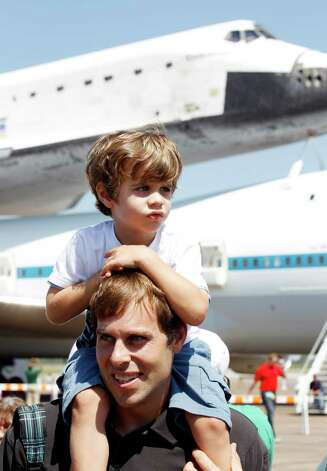 Four-year-old Miles Mataya of Friendswood gets a lift from his father Michael Mataya to view the Space Shuttle Endeavour and NASA's 747 Shuttle Carrier Aircraft at Ellington Field in Houston on Wednesday, Sept. 19, 2012. Endeavour will spend the night in Houston before continuing its journey from the Kennedy Space Center in Florida to the California Science Center in Los Angeles where it will be on permanent display. Photo: Kevin M. Cox, AP / The Galveston County Daily News