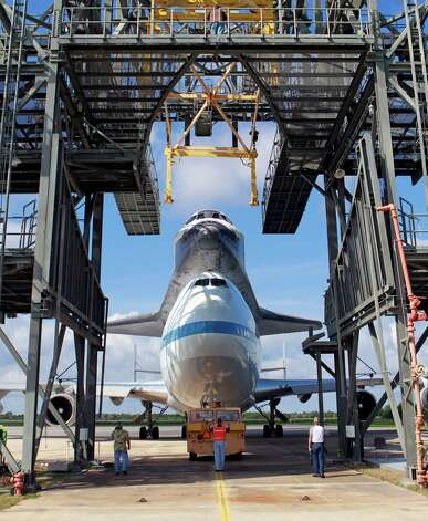 The space shuttle Endeavour atop a modified jumbo jet is moved to the mate/demate structure for protection from a forecasted storm at the Kennedy Space Center in Cape Canaveral, Fla. on Tuesday, Sept. 18, 2012. The weather system has delayed the retired spacecraft's departure to Los Angeles. Photo: John Raoux, AP / AP