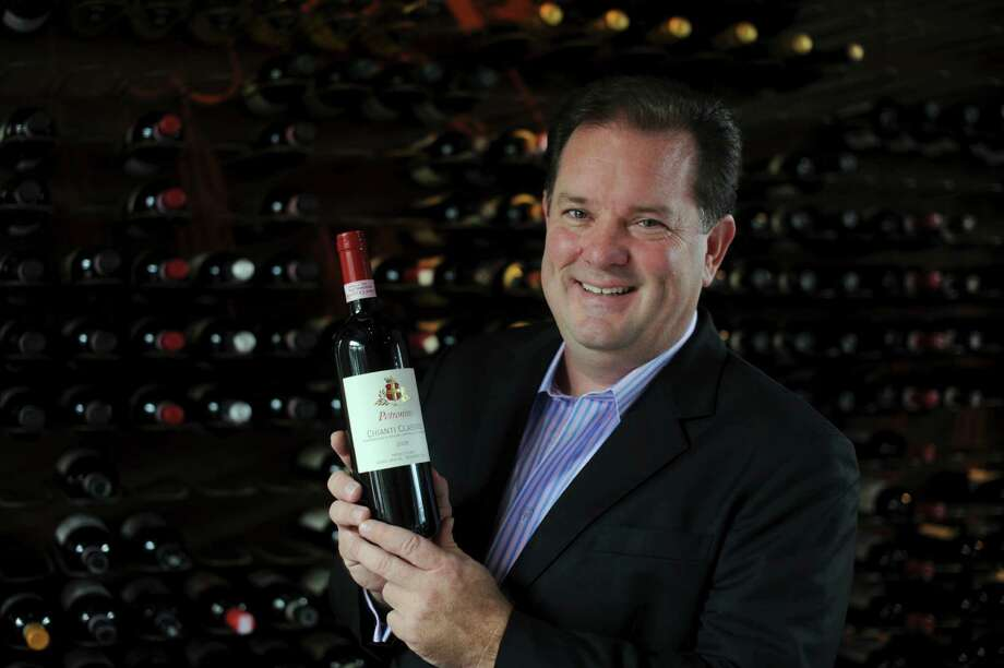 Keith Kuhn, president and founder of Serendipity Wines, was born and raised in San Antonio and has amassed a portfolio of more than 400 wines imported and exported internationally. Many are featured on the menu of Il Sogno. He holds a bottle of his favorite, a Petronius Chianti Classico 2009. Tuesday, Sept. 18 2012. Photo: Billy Calzada, San Antonio Express-News / © San Antonio Express-News