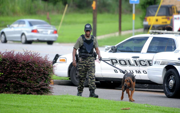 The Beaumont Police Department K-9 unit searches for a suspect in the robbery of SAFE Credit Union in Beaumont, Tuesday, July 24, 2012. Tammy McKinley/The Enterprise Photo: TAMMY MCKINLEY