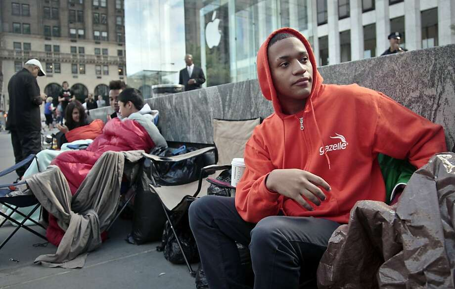 Joseph Cruz sets up his chair in line outside the Apple Store in Manhattan. Photo: Bebeto Matthews, Associated Press