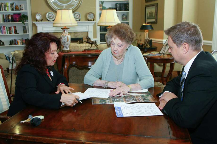 Rose Rios, left, director of sales and marketing at Village of Tanglewood, and Darren Skrehot, the community's executive director, discuss floor plans with Fran Short.