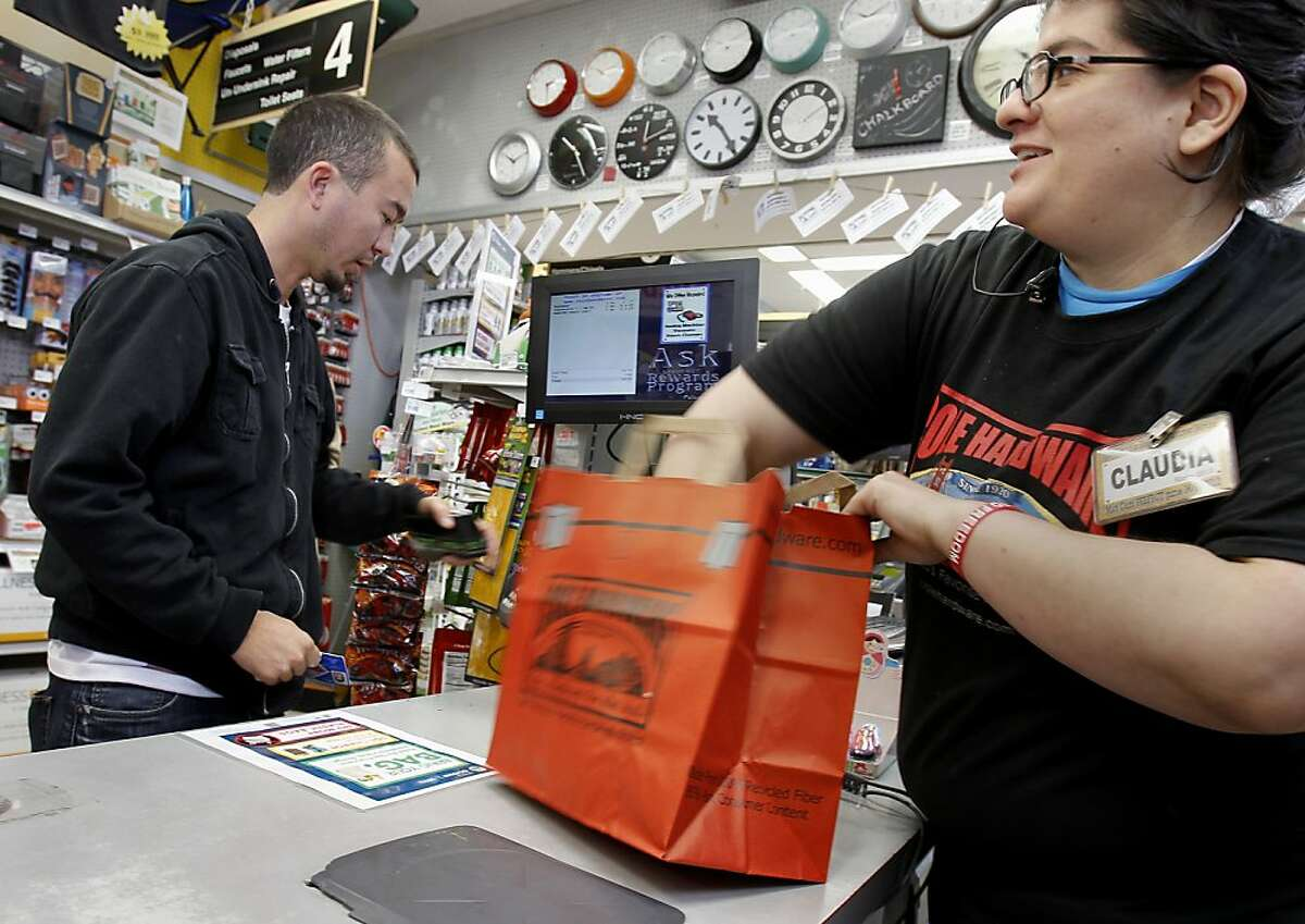 Cashier Claudia Villalon at Cole Hardware on Polk Street bags a purchase for customer Joe Bourque. On October 1 San Francisco's bag ordinance goes into effect charging 10 cents if a customer wants a bag. Cole Hardware, a San Francisco institution, is ahead of the game posting signs announcing the change and doing away with plastic bags years ago.