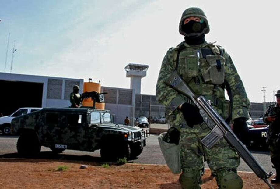 Mexican soldiers stand guard in front of Piedras Negras federal prison where a group of prisoners escaped on Sept. 18, 2012. Authorities say 132 inmates escaped, sparking a search by federal police and soldiers in an area close to the U.S. border. (AFP/GettyImages) (AFP/Getty Images)