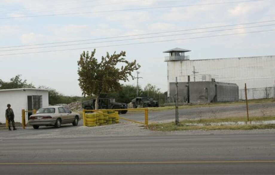 Mexican army soldiers guard an entrance to the prison on Sept. 18, 2012. Authorities were searching for inmates who fled the prison in Piedras Negras  across the border from Eagle Pass, Texas. (AP Photo/Adriana Alvarado) (Associated Press)