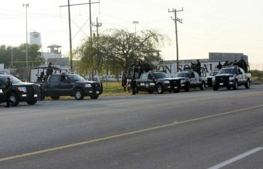 A group of Mexican federal police stand in front of the prison in Piedras Negras, Mexico, Monday Sept. 17, 2012. (AP Photo/Adriana Alvarado) (Associated Press)