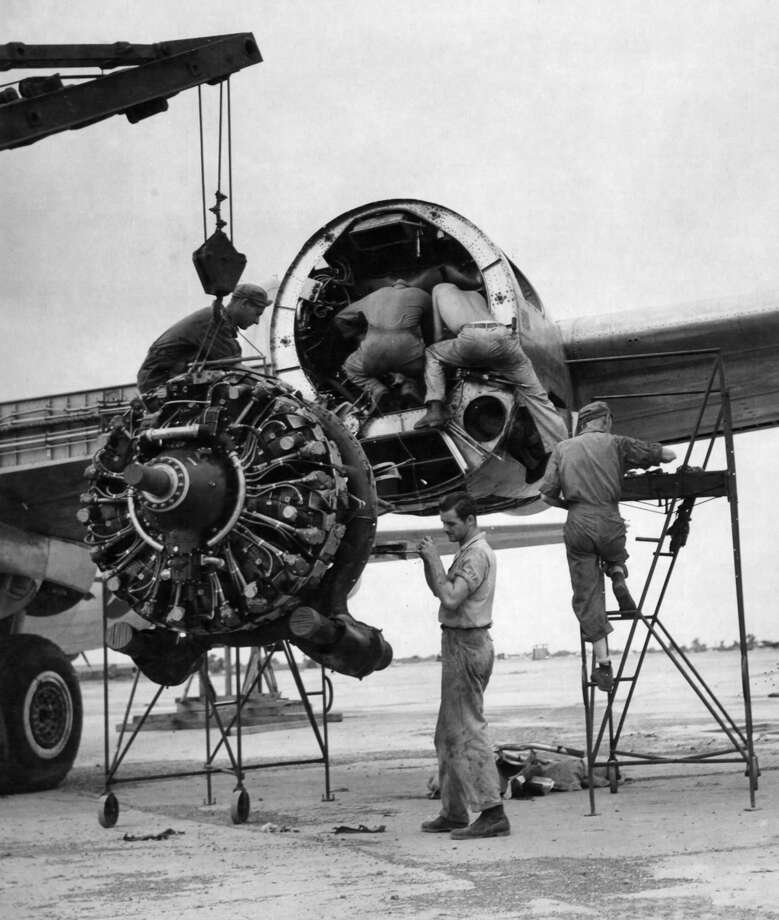 Mechanics guide a damaged engine of a Boeing B-29 Superfortress to the ground while three others inspect the engine casing. Photo: National Museum Of The U.S. Air Force