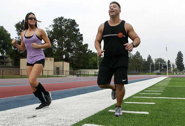 Fremont police officer Todd Young works out with personal trainer Melanie Wade at a local athletic field on Saturday, Sept. 15, 2012. Young nearly lost his life from gunshot wounds two years ago and just returned to active duty as a member of a multi-agency gang task force. Photo: Paul Chinn, The Chronicle