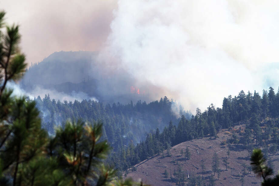 Flames from the Table Mountain wildfire burn a hillside southeast of Liberty Wednesday.  The smoke produced by the wildfire, along with current weather conditions, have contributed to reduce air quality in the area to dangerous levels. Photo: Ap