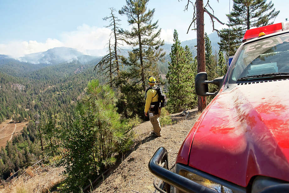 A firefighter watches the progress of the Table Mountain wildfire from a viewpoint at Boulder Lookout south of Liberty on Wednesday, Sept. 19, 2012.  The smoke produced by the wildfire, along with current weather conditions, have contributed to reduce air quality in the area to dangerous levels. Photo: Ap
