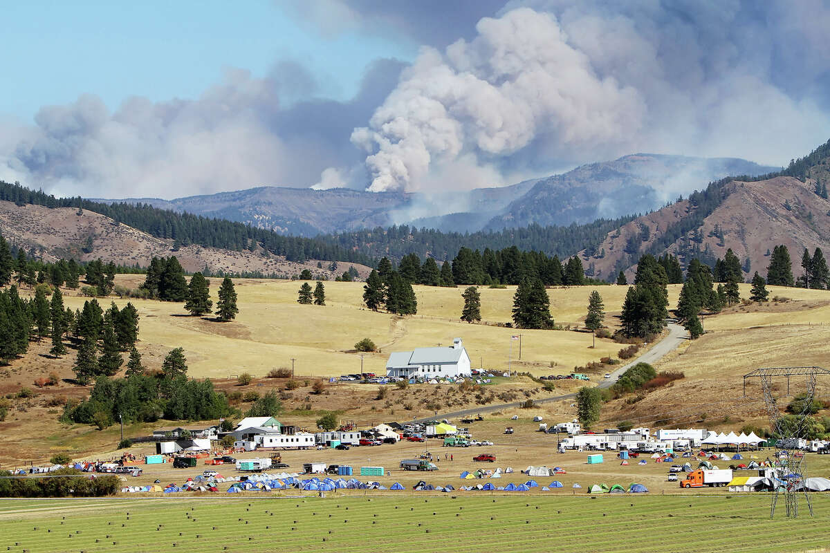 Smoke from the Table Mountain wildfire billows into the sky behind a fire camp set up at the Teanaway Grange Hall east of Cle Elum on Wednesday. The smoke produced by the wildfire, along with current weather conditions, have contributed to reduce air quality in the area to dangerous levels.