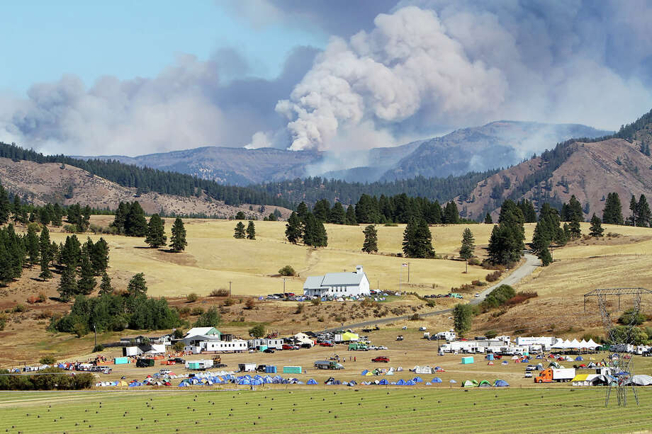 Smoke from the Table Mountain wildfire billows into the sky behind a fire camp set up at the Teanaway Grange Hall east of Cle Elum on Wednesday.  The smoke produced by the wildfire, along with current weather conditions, have contributed to reduce air quality in the area to dangerous levels. Photo: Ap