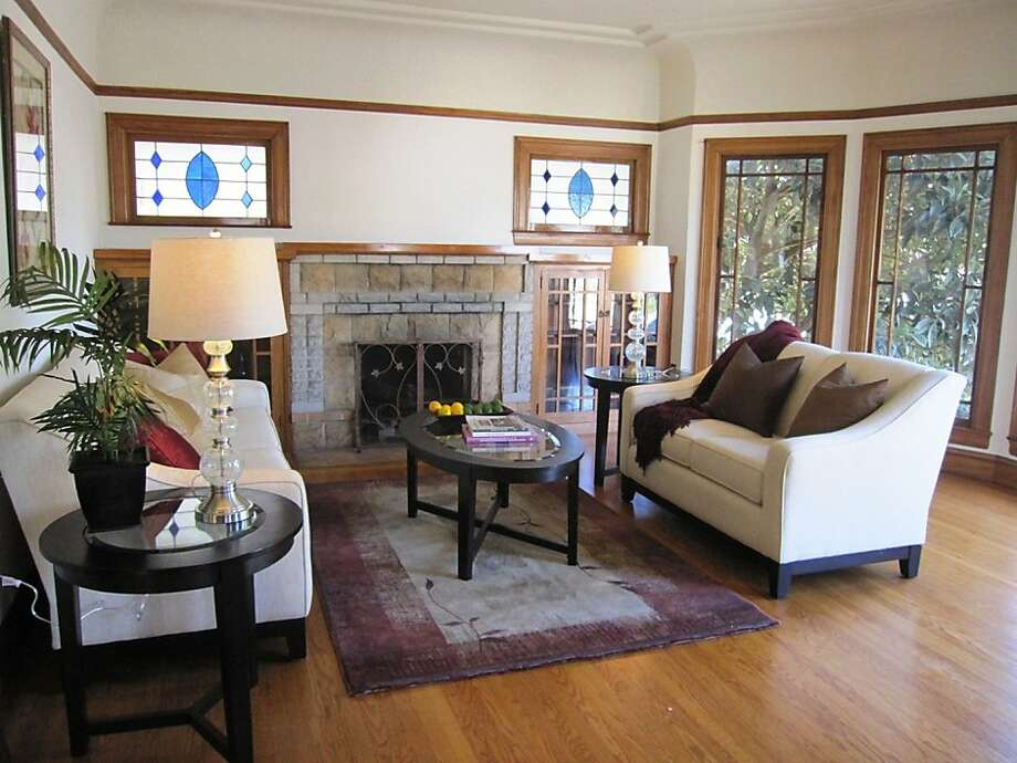 In addition to the brick fireplace, picture frame and stained-glass windows are among the period charms in the living room. Photo: Robin Young