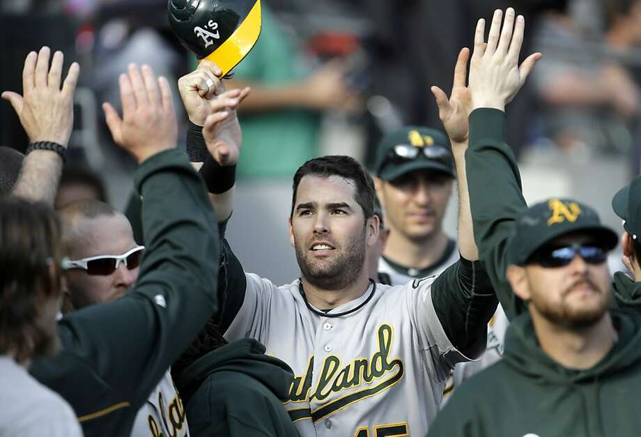 Oakland Athletics' Seth Smith is congratulated in the dugout after scoring on an RBI double by Josh Donaldson during the ninth inning of a baseball game against the Detroit Tigers, Thursday, Sept. 20, 2012, in Detroit.  (AP Photo/Paul Sancya) Photo: Paul Sancya, Associated Press