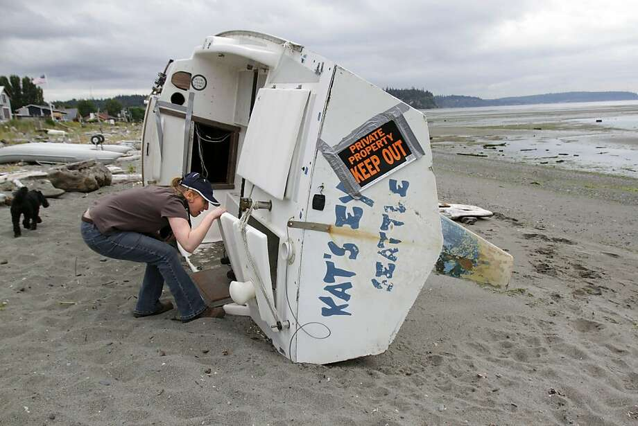 Melissa Ferris, who supervises the Derelict Vessel Removal Program in Washington state, inspect a boat. Photo: Mark Harrison, Associated Press