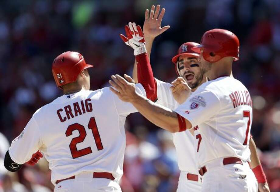 Cardinals' Allen Craig, left, is congratulated by teammates Matt Carpenter, center, and Matt Holliday after hitting a three-run home run during the first inning. (Jeff Roberson / Associated Press)