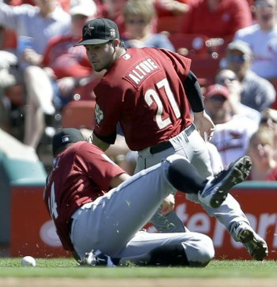 Astros right fielder Justin Maxwell, front, dives but misses a ball hit for a single by Cardinals' Matt Holliday as second baseman Jose Altuve watches during the first inning. (Jeff Roberson / Associated Press)