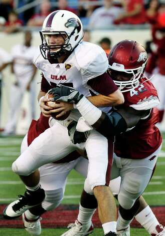 Louisiana Monroe quarterback Kolton Browning, left, is sacked by Arkansas defensive end Chris Smith (42) during the first quarter of an NCAA college football game in Little Rock, Ark., Saturday, Sept. 8, 2012. (AP Photo/Danny Johnston) Photo: Daniel Johnston, Associated Press / AP
