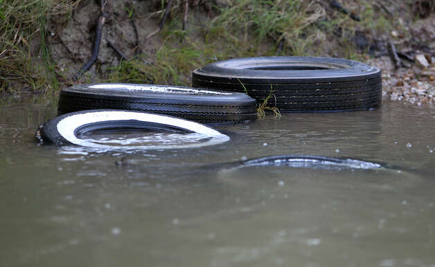 Discarded tires are seen along the banks of the San Antonio River along the Saspamco Paddling Trail in Southern Bexar County overseen by the San Antonio River Authority (SARA) on Thursday, Sept. 20, 2012. SARA is diligently working to rid debris from the river as a paddling trail is now open for public use. In two weeks, SARA will host a public opening event at the Helton San Antonio Nature Park which is situated at the end of the paddling trail in Wilson County. The start of the 12-mile long paddling trail is about 20 miles from downtown San Antonio. Photo: Kin Man Hui, SAN ANTONIO EXPRESS-NEWS / ©2012 San Antonio Express-News