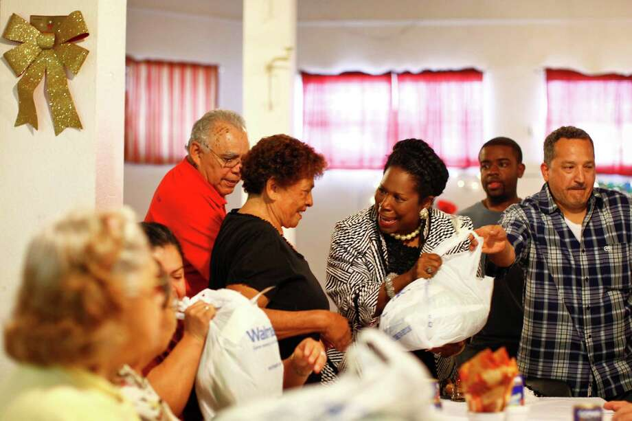 U.S. Congresswoman Sheila Jackson Lee helps distribute a turkey to Delfina Martinez as Joe Perez looks on at the Latino Learning Center during the 16th annual turkey giveaway Tuesday, Nov. 23, 2010, in Houston. Photo: Michael Paulsen, Houston Chronicle / Houston Chronicle