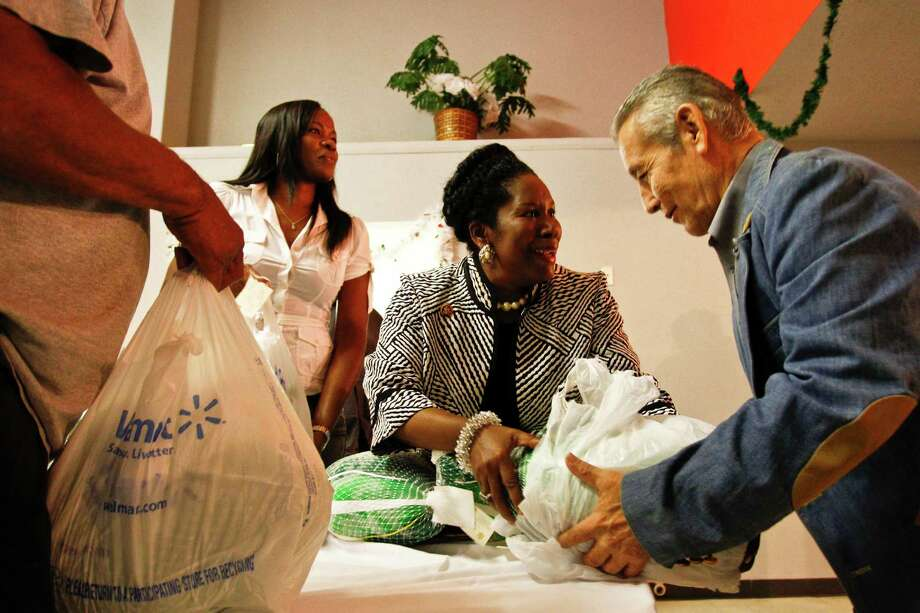 Former basketball star Sheryl Swoopes and Sheila Jackson Lee help distribute a turkey to Jose Montalvo at the Latino Learning Center during the 16th annual turkey giveaway Tuesday, Nov. 23, 2010, in Houston. Photo: Michael Paulsen, Houston Chronicle / Houston Chronicle