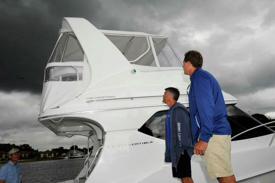 John Metaxas, of Madison, and Don Gesick, of Clinton, look at boats at the Norwalk Boat Show Thursday, Sept. 20, 2012. The Norwalk Boat Show, a in-water boat show, runs Thursday through Sunday September 20-23, 2012 10am-6pm daily. Photo: Helen Neafsey / Greenwich Time