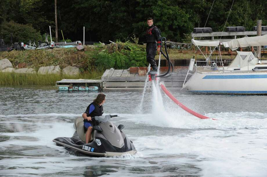 Aaron Gould, right, of San Diego, CA, flyboarding with help with Evan Fyte, of Orlando, Fla. at the Norwalk Boat Show, Thursday, Sept. 20, 2012. The Norwalk Boat Show, in-water boat show, runs Thursday through Sunday September 20-23, 2012 10am-6pm daily. Photo: Helen Neafsey / Greenwich Time