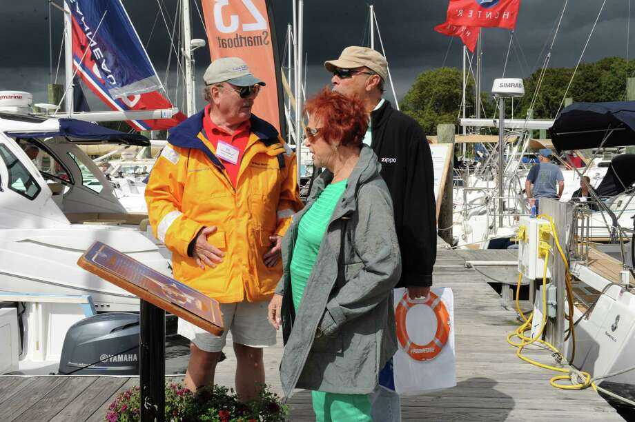 Ed Hellenbrecht, left, helping Shelly and Paul Baron looking at the boats at the Norwalk Show Thursday, Sept. 20, 2012. The Norwalk Boat Show, a in-water boat show, runs Thursday through Sunday September 20-23, 2012 10am-6pm daily. Photo: Helen Neafsey / Greenwich Time