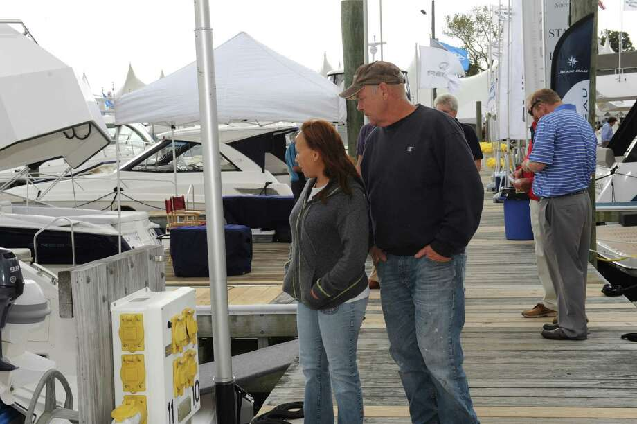 Patricia and Tom Wilson, of Norwalk, looks at boat at the Norwalk Boat Show Thursday, Sept. 20, 2012. Norwalk Boat Show, a in-water boat show, runs Thursday through Sunday September 20-23, 2012 10am-6pm daily. Photo: Helen Neafsey / Greenwich Time