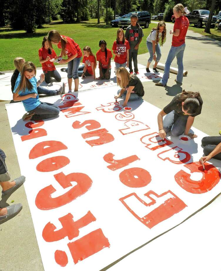 Kountze High School cheerleaders and other children work on a large sign Wednesday, Sept. 19, 2012 in Kountze, Texas.  The small Hardin County community is rallying behind the high school's cheerleaders after the squad members were told they could not use scripture verses on their signs at the football games. (AP Photo/The Beaumont Enterprise, Dave Ryan) Photo: Dave Ryan, Associated Press / The Beaumont Enterprise
