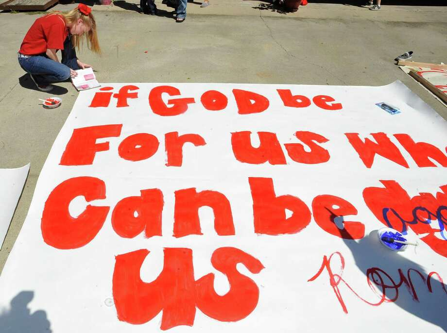 Andrea Lawrence double checks her bible while working on a big sign.  Kountze cheerleaders, friends and supportive parents who are standing up for their kids and their beliefs, were making signs and painting car windows Wednesday afternoon that will be seen around Kountze in support of the cheerleaders who were told they could not put scripture on their football signs.  Each game this season, the Kountze cheerleaders have made Christian-themed run-through signs for the football players. The signs, which featured scripture verses, went viral and have now been stopped by the school district's leaders who were told by a group the signs were offensive and against the separation of church and state. Dave Ryan/The Enterprise Photo: Dave Ryan, Dave Ryan/The Enterprise