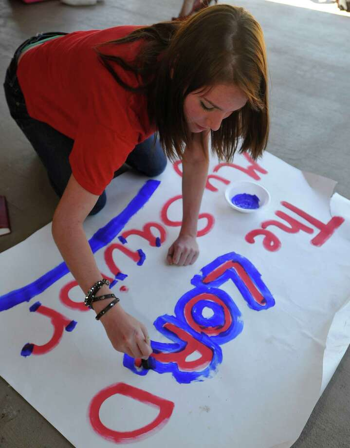 Ashton Lawrence, a cheerleader, enhances her latest piece of work on the patio. Kountze cheerleaders, friends and supportive parents who are standing up for their kids and their beliefs, were making signs and painting car windows Wednesday afternoon that will be seen around Kountze in support of the cheerleaders who were told they could not put scripture on their football signs.  Each game this season, the Kountze cheerleaders have made Christian-themed run-through signs for the football players. The signs, which featured scripture verses, went viral and have now been stopped by the school district's leaders who were told by a group the signs were offensive and against the separation of church and state. Dave Ryan/The Enterprise Photo: Dave Ryan, Dave Ryan/The Enterprise