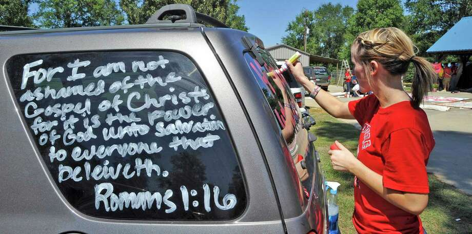 Brooke Coates, a cheerleader, paints more verse on another car.   Kountze cheerleaders, friends and supportive parents who are standing up for their kids and their beliefs, were making signs and painting car windows Wednesday afternoon that will be seen around Kountze in support of the cheerleaders who were told they could not put scripture on their football signs.  Each game this season, the Kountze cheerleaders have made Christian-themed run-through signs for the football players. The signs, which featured scripture verses, went viral and have now been stopped by the school district's leaders who were told by a group the signs were offensive and against the separation of church and state. Dave Ryan/The Enterprise Photo: Dave Ryan, Dave Ryan/The Enterprise