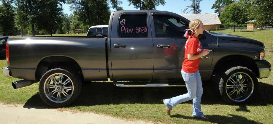 Morgan Coplen, a cheerleader, writes a proverb number on the side windshield of a truck. Kountze cheerleaders, friends and supportive parents who are standing up for their kids and their beliefs, were making signs and painting car windows Wednesday afternoon that will be seen around Kountze in support of the cheerleaders who were told they could not put scripture on their football signs.  Each game this season, the Kountze cheerleaders have made Christian-themed run-through signs for the football players. The signs, which featured scripture verses, went viral and have now been stopped by the school district's leaders who were told by a group the signs were offensive and against the separation of church and state. Dave Ryan/The Enterprise Photo: Dave Ryan, Dave Ryan/The Enterprise
