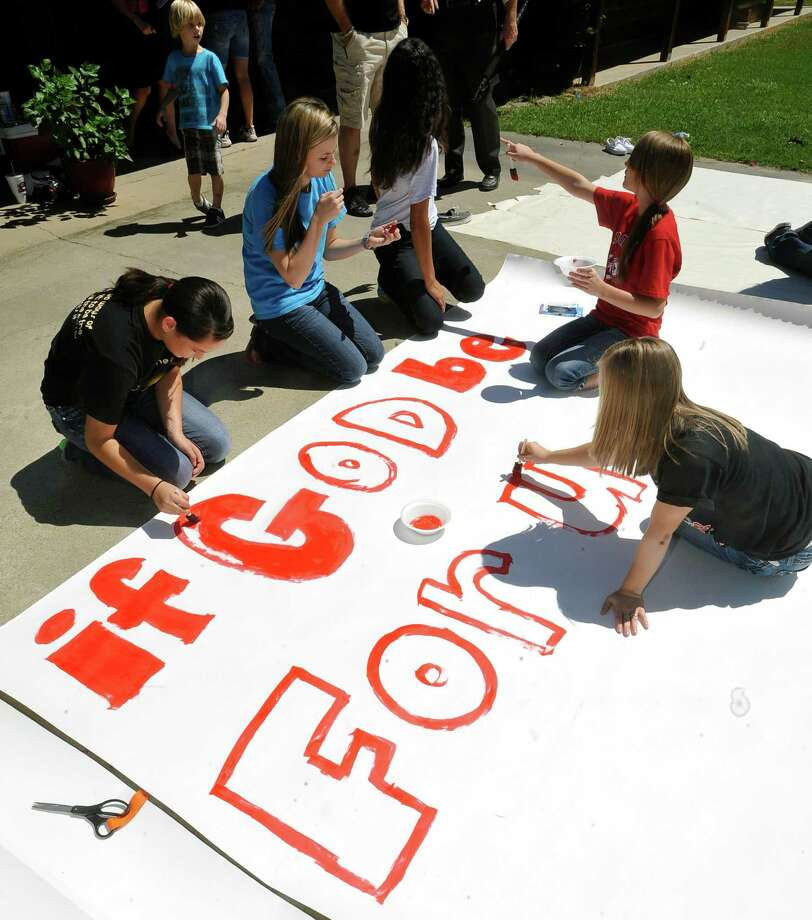 The kids work on a large sign in the driveway that required some of the kids to sit on the sign to keep it from blowing in the breeze.  Kountze cheerleaders, friends and supportive parents who are standing up for their kids and their beliefs, were making signs and painting car windows Wednesday afternoon that will be seen around Kountze in support of the cheerleaders who were told they could not put scripture on their football signs.  Each game this season, the Kountze cheerleaders have made Christian-themed run-through signs for the football players. The signs, which featured scripture verses, went viral and have now been stopped by the school district's leaders who were told by a group the signs were offensive and against the separation of church and state. Dave Ryan/The Enterprise Photo: Dave Ryan, Dave Ryan/The Enterprise