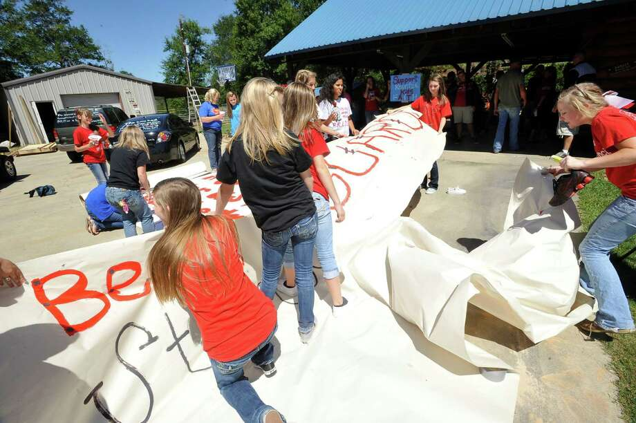 The kids wrestle a large sign in the driveway that did not have enough weight on it to keep it from blowing in the breeze and ripping.  Kountze cheerleaders, friends and supportive parents who are standing up for their kids and their beliefs, were making signs and painting car windows Wednesday afternoon that will be seen around Kountze in support of the cheerleaders who were told they could not put scripture on their football signs.  Each game this season, the Kountze cheerleaders have made Christian-themed run-through signs for the football players. The signs, which featured scripture verses, went viral and have now been stopped by the school district's leaders who were told by a group the signs were offensive and against the separation of church and state. Dave Ryan/The Enterprise Photo: Dave Ryan, Dave Ryan/The Enterprise