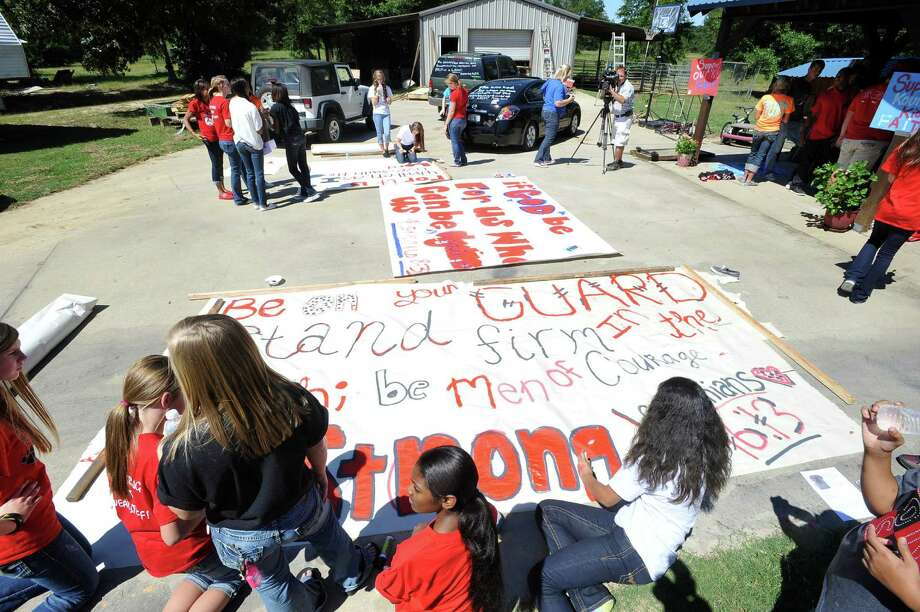 Kountze cheerleaders, friends and supportive parents who are standing up for their kids and their beliefs, were making large signs and painting car windows Wednesday afternoon that will be seen around Kountze in support of the cheerleaders who were told they could not put scripture on their football signs.  Each game this season, the Kountze cheerleaders have made Christian-themed run-through signs for the football players. The signs, which featured scripture verses, went viral and have now been stopped by the school district's leaders who were told by a group the signs were offensive and against the separation of church and state. Dave Ryan/The Enterprise Photo: Dave Ryan, Dave Ryan/The Enterprise