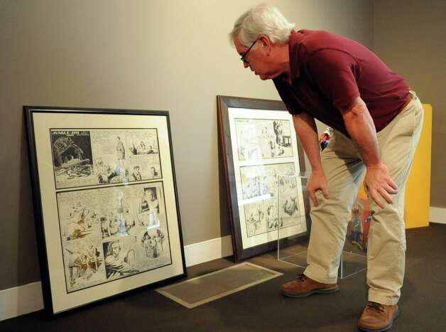 "Brian Walker points out artwork and memorabilia as it is set up for the upcoming exhibit ""Flash Gordon and the Heroes of the Universe"" at the Stamford Museum and Nature Center on Thursday, September 13, 2012. The exhibit opens the weekend of September 22. Photo: Lindsay Niegelberg / Stamford Advocate"