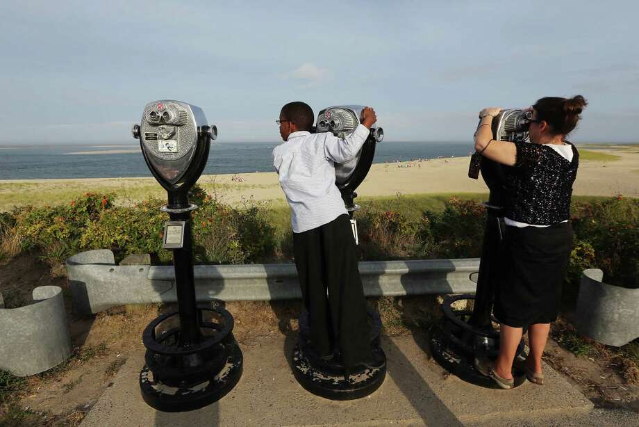 CHATHAM, MA - AUGUST 12:  People watch the ocean with binoculars on Lighthouse Beach on Cape Cod on August 12, 2012 in Chatham, Massachusetts. A man was confirmed to have been bitten by a great white shark less than two weeks ago in the ocean near the shoreline of Truro in Cape Cod. An increase in the seal population on Cape Cod has led to increased shark sightings including great whites in the waters off Chatham. (Photo by Mario Tama/Getty Images) Photo: Mario Tama / 2012 Getty Images