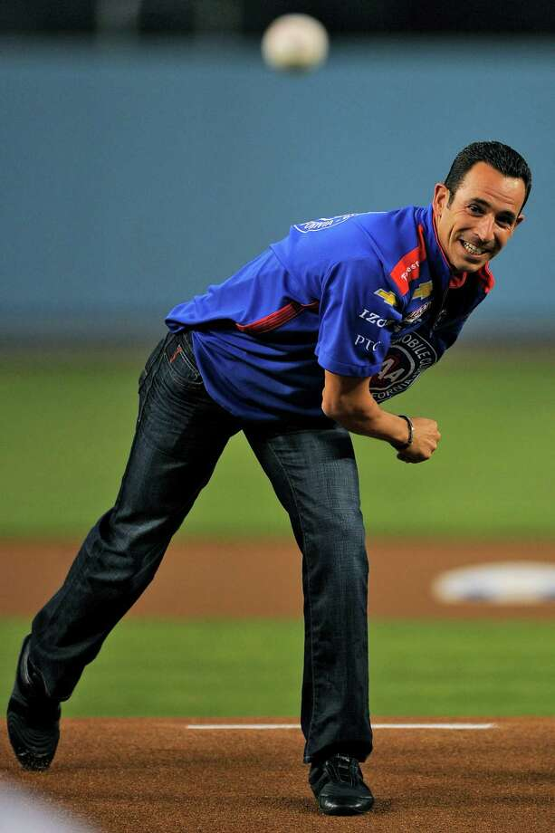 Race car driver Helio Castroneves throws out the ceremonial first pitch prior to the Los Angeles Dodgers' baseball game against the St. Louis Cardinals, Thursday, Sept. 13, 2012, in Los Angeles. (AP Photo/Mark J. Terrill) Photo: Mark J. Terrill