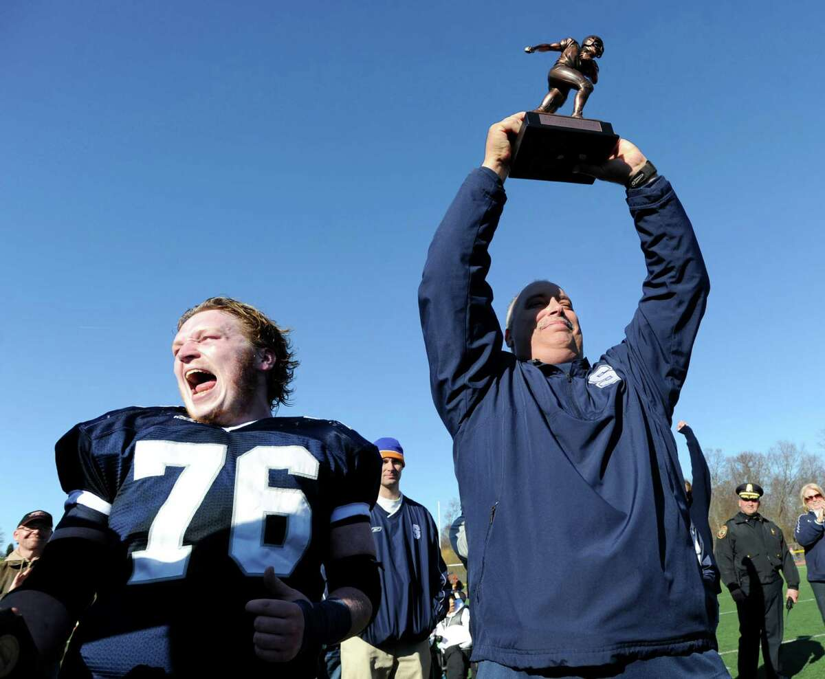 Jack Gibson # 76 of Staples High School shouts out as his coach Marce Petroccio holds the McDougall Trophy over his head at the conclusion of the FCIAC Football Championship game in which Staples High School defeated Greenwich High School 31-27 at Staples, Westport, Thursday afternoon, Nov. 24, 2011.