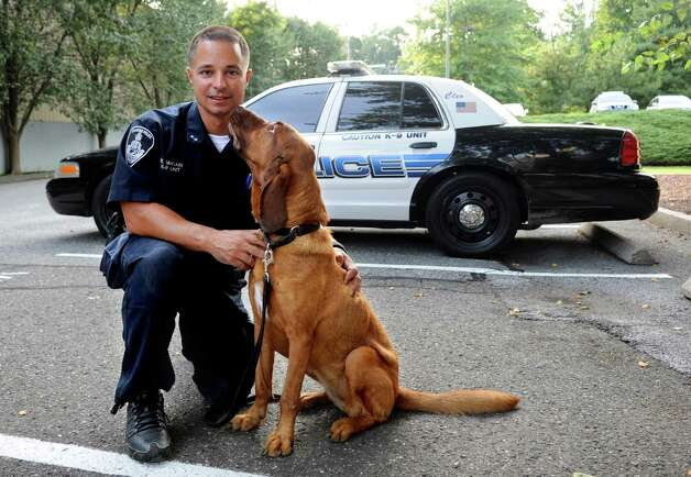 Cleo, a bloodhound with the Stamford Police Department, stands with Officer Robert Macari on Friday, September 14, 2012. Photo: Lindsay Niegelberg / Stamford Advocate