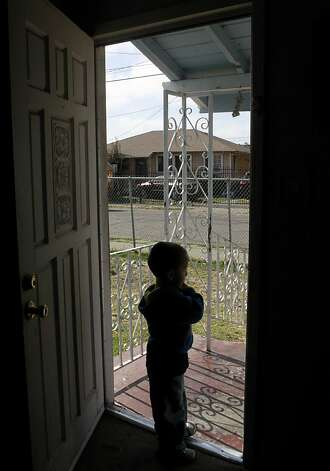 Rodolfo Del Real, 3, stands at the front door of the East Oakland home where his 11-year-old cousin was injured in a hail of gunfire while sleeping. Photo: Paul Chinn, The Chronicle