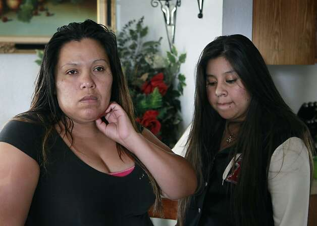 Ana Dalia Hernandez (left) and her daughter Angelina Duenas gather in the dining room after Hernandez's 11-year-old son, Luis Duenas, was hit by a bullet that traveled through three walls in a drive-by shooting in Oakland, Calif. on Thursday, Sept. 20, 2012. Duenas was sleeping in his bed when gunmen pumped several rounds into the home at about 1 a.m. Photo: Paul Chinn, The Chronicle