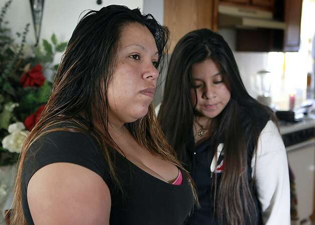 Ana Dalia Hernandez (left) and daughter Angelina Duenas discuss the hail of bullets that injured Hernandez's 11-year-old son in their East Oakland home. Photo: Paul Chinn, The Chronicle