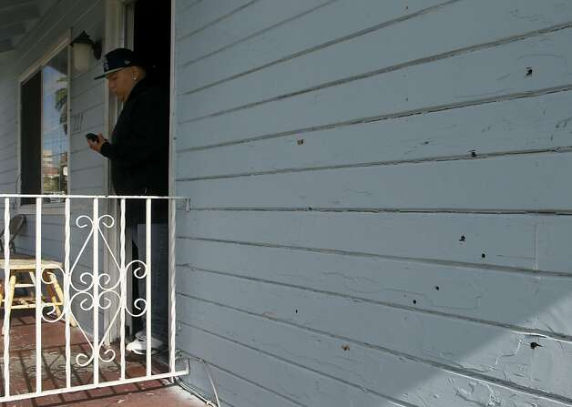 Bullet holes remain on the front wall of Francisco Duenas' (left) home after his 11-year-old brother Luis,  was injured by a bullet that traveled through three walls in a drive-by shooting in Oakland, Calif. on Thursday, Sept. 20, 2012. Duenas was sleeping in his bed when gunmen pumped several rounds into the home at about 1 a.m. Photo: Paul Chinn, The Chronicle