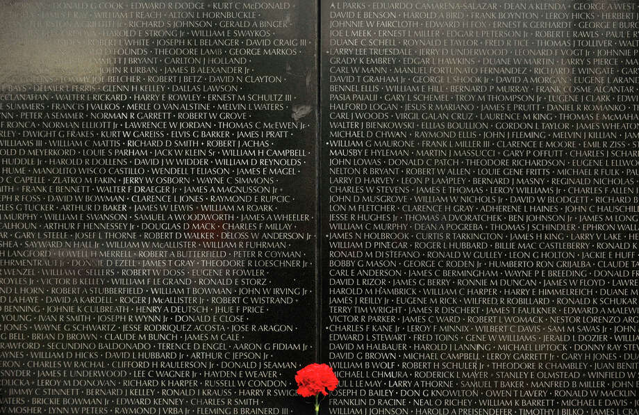 A red carnation is propped among the names of the servicemen who died or are missing in action at the Dignity Memorial Vietnam Wall in front of the War Memorial at Rogers Park in Danbury on Thursday, Sept. 20, 2012. Photo: Jason Rearick / The News-Times