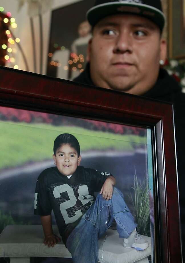 Francisco Duenas, 16, holds a photograph of his 11-year-old brother, Luis, who was hit by a bullet that traveled through three walls in a drive-by shooting in Oakland, Calif. on Thursday, Sept. 20, 2012. Luis was sleeping in his bed when gunmen pumped several rounds into the home at about 1 a.m. Photo: Paul Chinn, The Chronicle